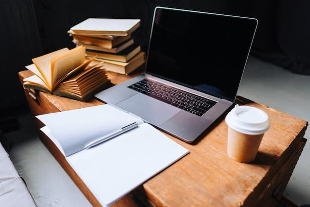 Laptopcomputer op de houten tafel met boeken, notitieboekje en kopje koffie in de ochtend. Premium Foto