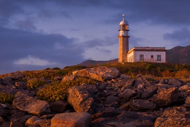 Larino lighthouse omgeven door rotsen tijdens de zonsondergang in spanje Gratis Foto