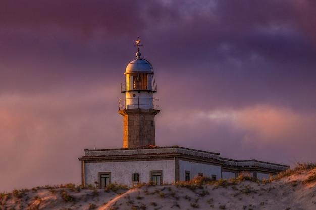 Larino lighthouse onder een bewolkte hemel tijdens de zonsondergang in de avond in spanje Gratis Foto