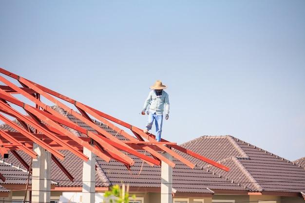 Lasser bouwvakkers installeren stalen framestructuur van het dak van het huis op de bouwplaats met wolken en lucht te bouwen Premium Foto