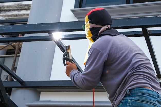 Lasser is de stalen constructie aan het lassen om aan het huis toe te voegen. Premium Foto