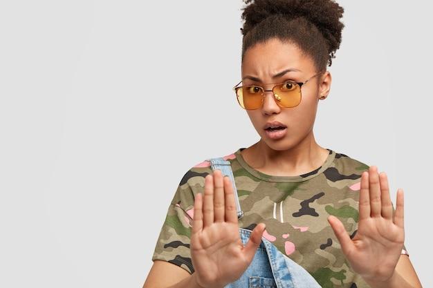 Lastige camouflagevrouw die tegen de witte muur poseert Gratis Foto