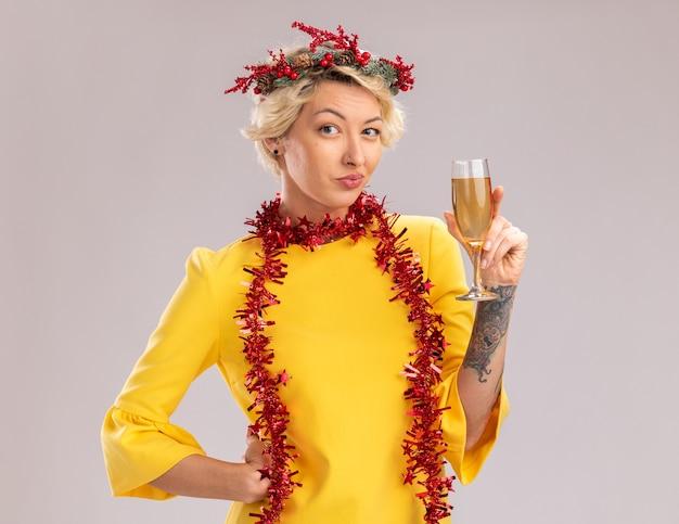 Lastige jonge blonde vrouw hoofd kerstkrans en klatergoud garland dragen rond nek met glas champagne houden hand op taille kijken camera geïsoleerd op witte achtergrond Gratis Foto
