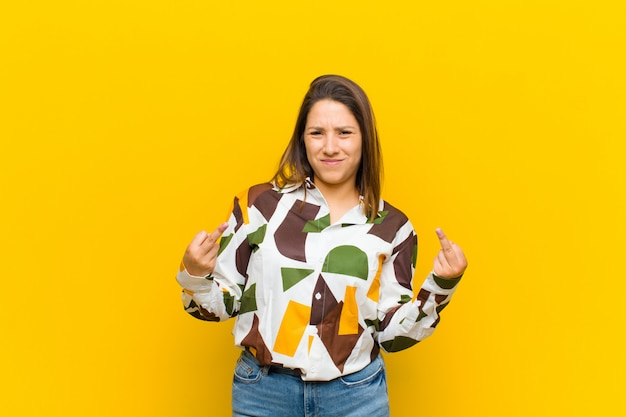 Latijns-amerikaanse vrouw die zich provocerend, agressief en obsceen voelt, de middelvinger omdraait, met een rebelse houding over de gele muur Premium Foto