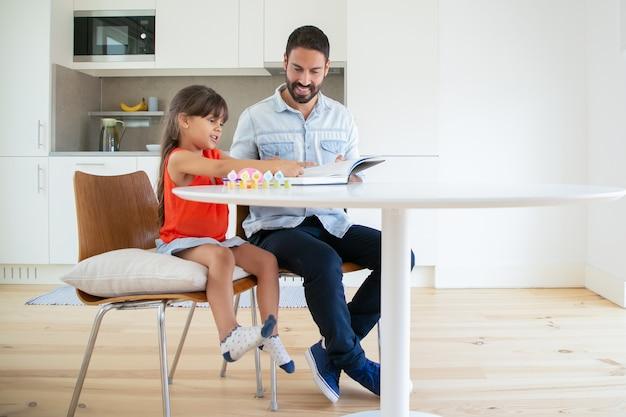 Latijnse vader met boek voor dochter en lachend. Gratis Foto