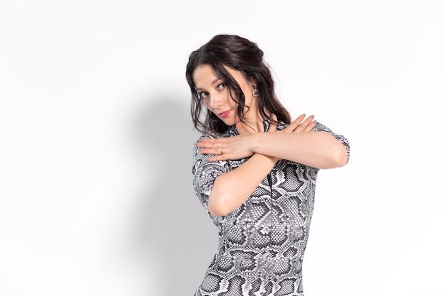 Latina-dans, stripdans, hedendaags en bachata-damesconcept - vrouw die improvisatie danst en haar lange haar beweegt op een witte muur. Premium Foto