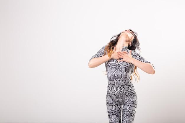 Latino dans, improvisatie, eigentijds en mode dansconcept - jonge mooie vrouw die op witte studiomuur danst. Premium Foto
