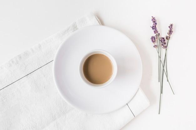 Lavendel en kopje koffie op servet over witte achtergrond Gratis Foto