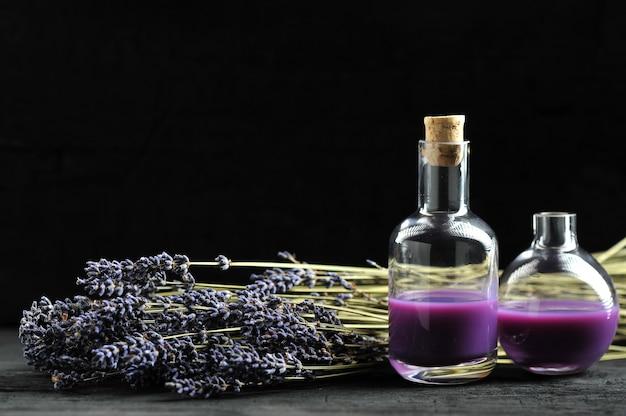 Lavendel, lavendelolie op donkere houten achtergrond met ruimte voor tekst Premium Foto
