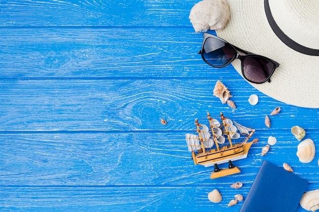 Lay-out van zeeschelpen dichtbij stuk speelgoed schip en zonnebril met hoed Gratis Foto