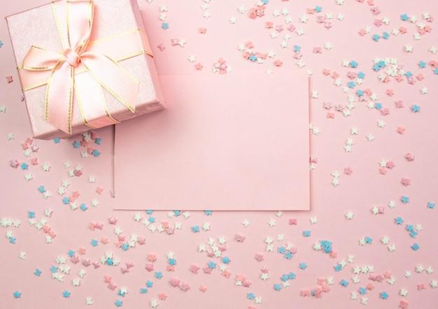 Lay-out voor opname. roze blad om te schrijven en een geschenkdoos op een roze achtergrond met decoratieve veelkleurige elementen met sterren en strikken. plat lag, bovenaanzicht Premium Foto