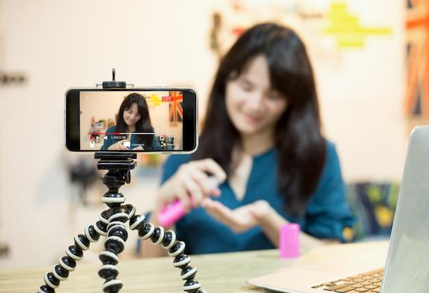 Leef videoblogger jong vlogger-meisje live uitgezonden over cosmetische inhoud via mobiel Premium Foto