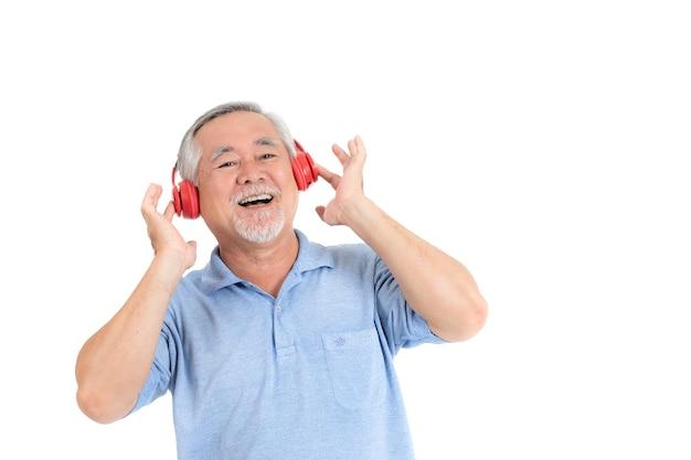 Leeft de levensstijl hogere mens gelukkig genieten van het luisteren muziek met hoofdtelefoons op witte ba wordt geïsoleerd die Premium Foto