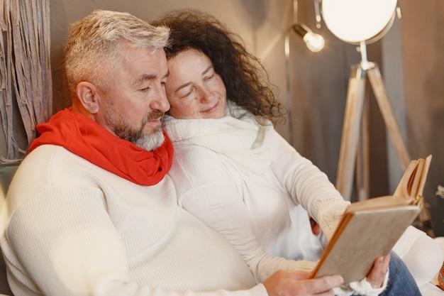 Leeftijd en mensen concept. hoger paar thuis. vrouw in een witte gebreide trui. Gratis Foto