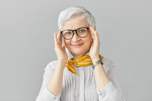 Leeftijd, optica, brillen en visieconcept. glimlachend goed uitziende elegante gepensioneerde volwassen vrouw met vrolijke gelaatsuitdrukking, stijlvolle bril in zwart frame aanpassen, shirt en sjaal dragen Gratis Foto