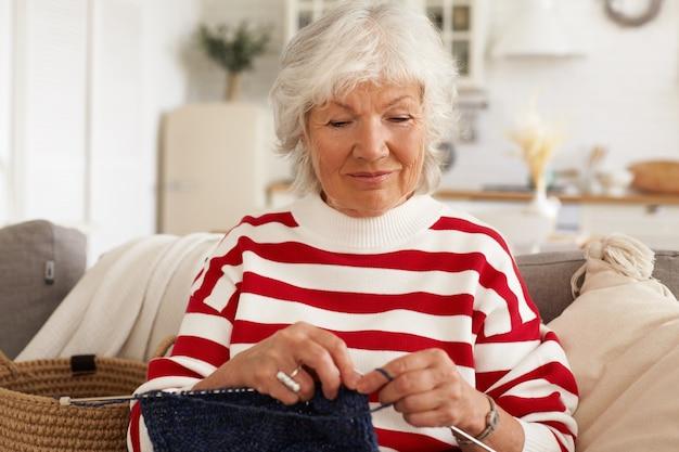 Leeftijd, vrije tijd, hobby en pensioenconcept. aantrekkelijke stijlvolle kaukasische vrouwelijke gepensioneerde m / v in gestreepte wit rode trui zittend op de bank in gezellig interieur met naalden en garen, sjaal of muts breien Gratis Foto