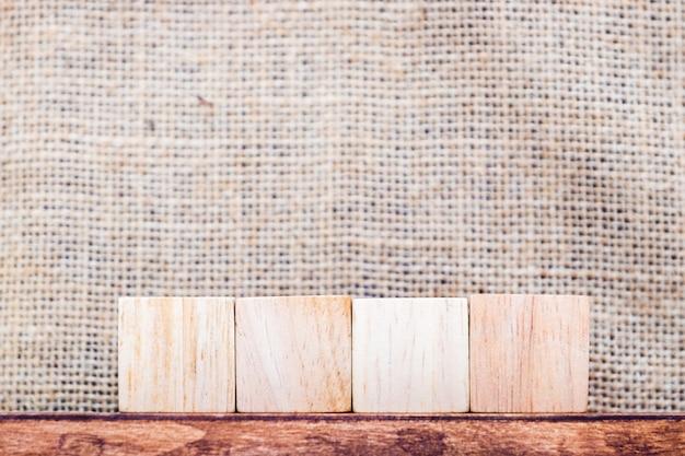 Leeg 4 stuk kubushout op houten lijst en de muur van de zakstof Premium Foto