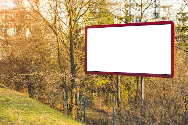 Leeg aanplakbord of groot bord met klein bos en appartementen. reclame leeg Premium Foto