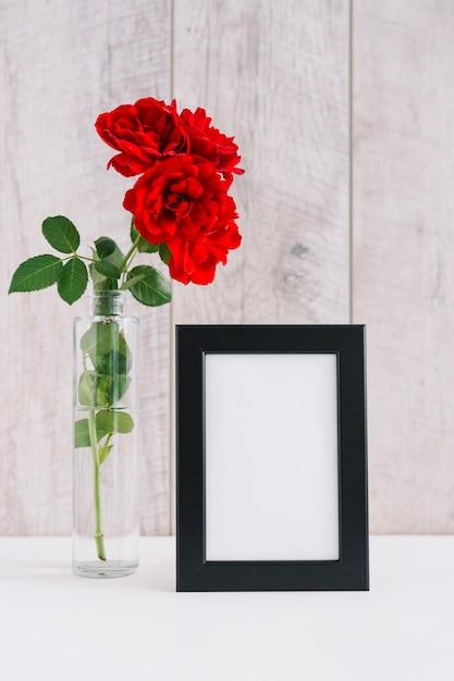 Leeg afbeeldingsframe en mooie rode bloemen in vaas Gratis Foto