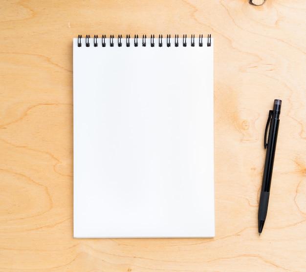 Leeg blad van notitieboekje met een spiraal op een neutrale beige houten achtergrond, hoogste mening. Premium Foto
