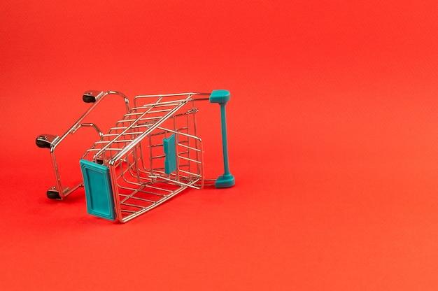 Leeg boodschappenwagentje op heldere rode achtergrond Premium Foto