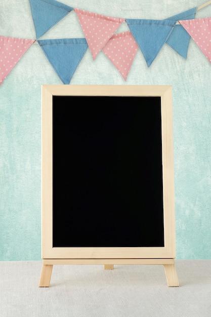 Leeg bord die zich over kleurrijke partijvlaggen bevinden die op groene muurachtergrond hangen met exemplaarruimte voor tekst Premium Foto
