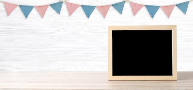 Leeg bord die zich over kleurrijke partijvlaggen bevinden die op witte houten achtergrond met exemplaarruimte hangen voor tekst Premium Foto