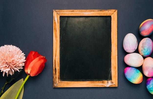 Leeg bord met rode tulp; chrysant en paaseieren op zwarte achtergrond Gratis Foto