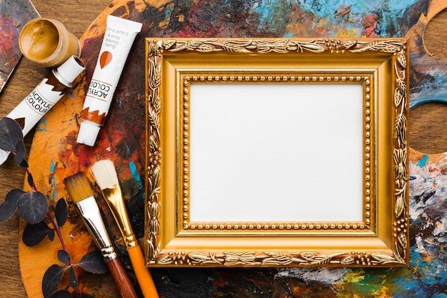 Leeg canvas in gouden frame en verf Gratis Foto