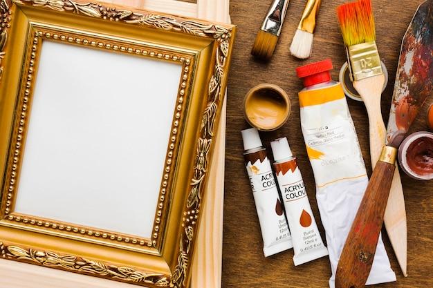 Leeg canvas in gouden frame en verfborstels Gratis Foto