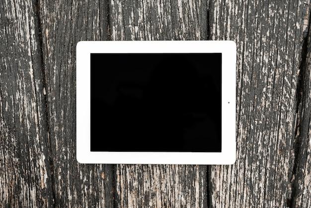 Leeg digitaal tabletapparaat op houten geweven achtergrond Gratis Foto