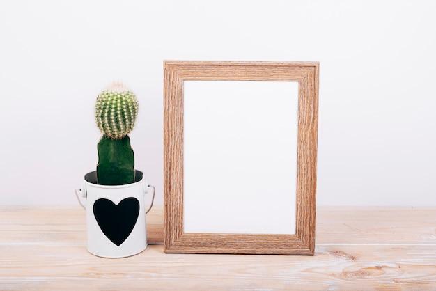 Leeg fotokader en succulente installatie met heartshape op pot over houten lijst Premium Foto