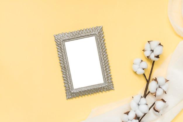 Leeg frame met katoenen tak op gele lijst Gratis Foto