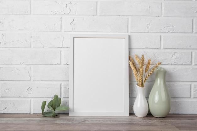 Leeg frame op plank naast vaas Gratis Foto