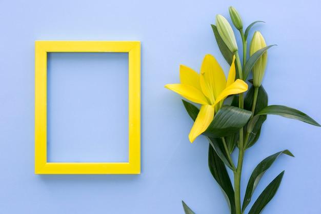 Leeg geel fotokader met leliebloemen op blauwe oppervlakte Gratis Foto
