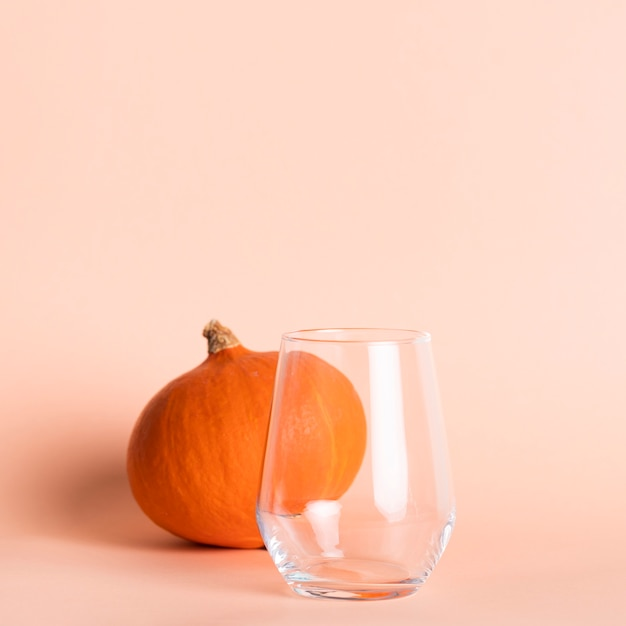 Leeg glas dichtbij kleine pompoen Gratis Foto