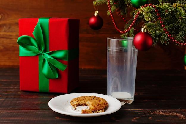 Leeg glas melk en kruimelkoekjes en een geschenk onder de kerstboom. de komst van de kerstman. Premium Foto