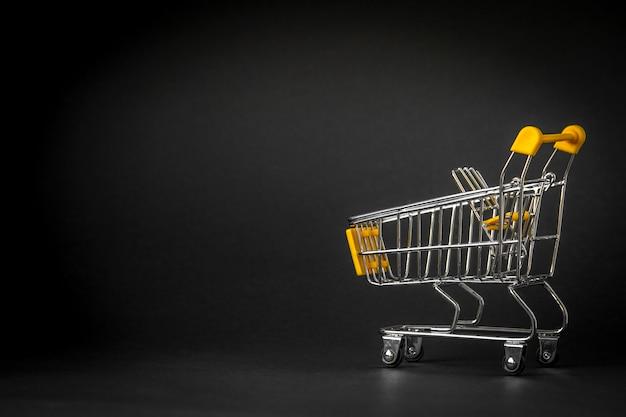 Leeg het winkelen karretje op donkere gestemde achtergrond met wat exemplaarruimte Premium Foto