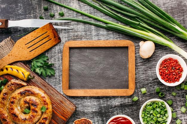 Leeg houten lei dat door geroosterde worsten en vers ingrediënt wordt omringd Gratis Foto