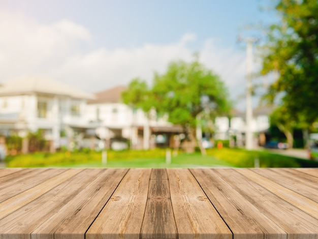 Leeg houten tafelblad op blur abstract groen van tuin en huis in