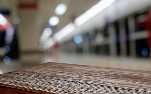 Leeg houten tafelruimte platform en wazige koffie winkel waar werk en ontmoetingsplaats achtergrond voor product display montage. selectieve focus. Gratis Foto