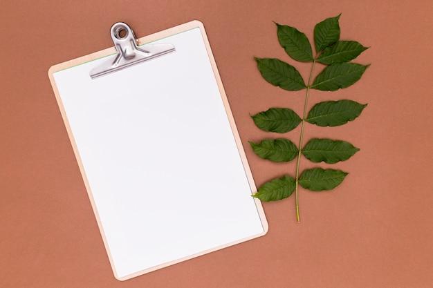 Leeg klembord met takjebladeren Gratis Foto