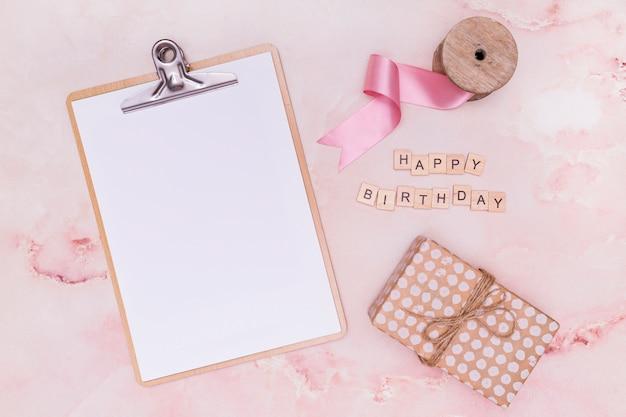 Leeg klembord naast verjaardagslevering Gratis Foto