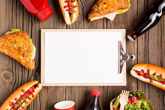 Leeg klembord omringd door fast food Gratis Foto