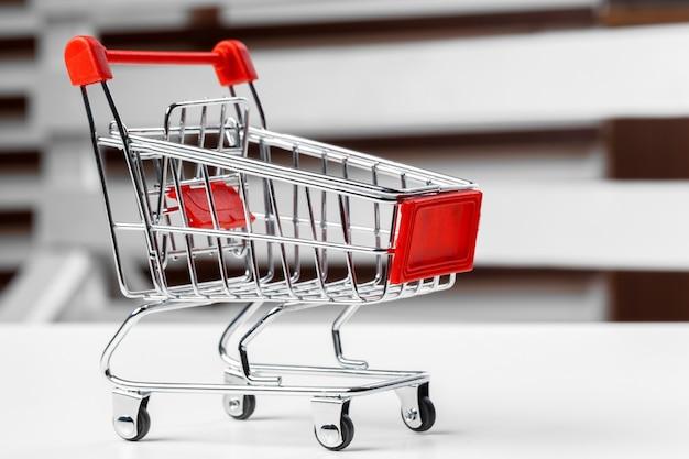 Leeg kruidenierswinkelstuk speelgoed boodschappenwagentje op een lijst Premium Foto