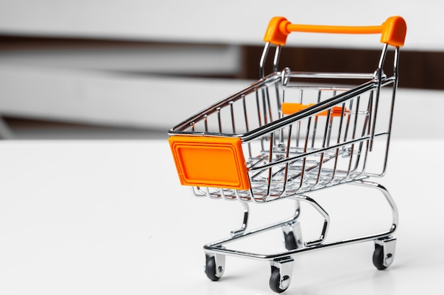 Leeg kruidenierswinkelstuk speelgoed boodschappenwagentje op lijst Premium Foto
