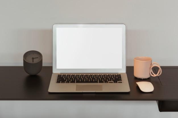 Leeg laptopscherm en een roze koffiekop Gratis Foto