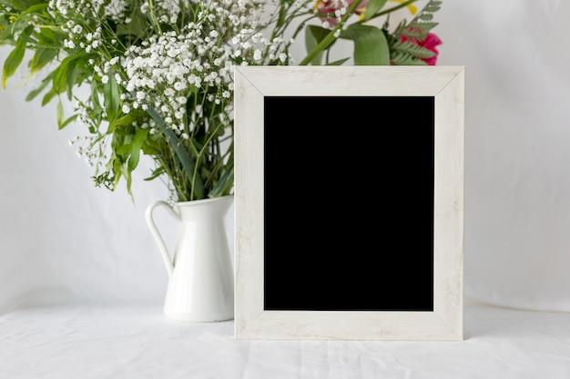 Leeg leeg fotokader met bloemvaas op witte lijst Gratis Foto