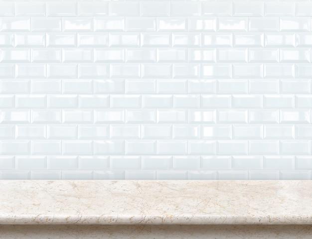 Leeg marmeren tafelblad met glanzende keramische witte tegelmuur. Premium Foto