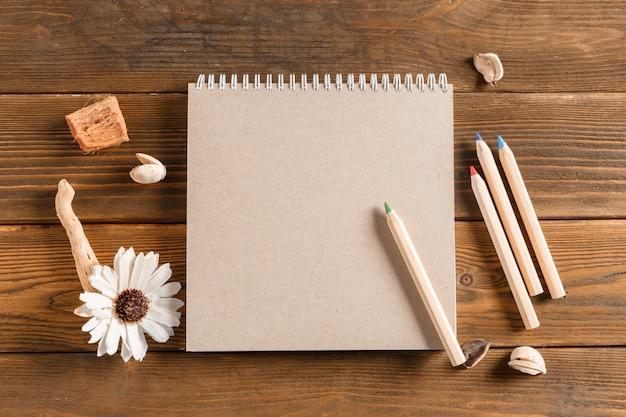 Leeg notitieboekje met bloem op uitstekende houten lijst Premium Foto